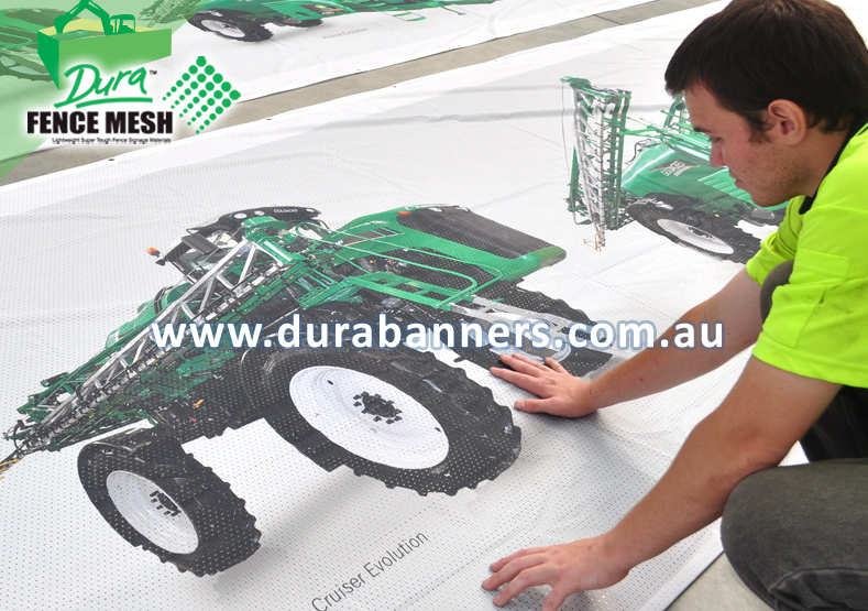 Shows a large agricultural machine printed on a banner sign mesh for display at the outdoor event