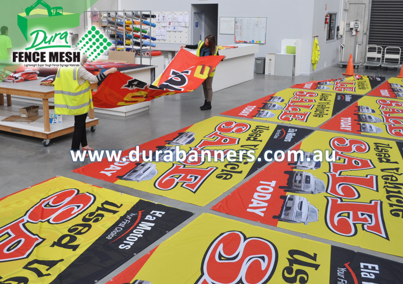 Many Banner Flags laid out in preparation to send the customer order of banner signs for a Car Sale Event
